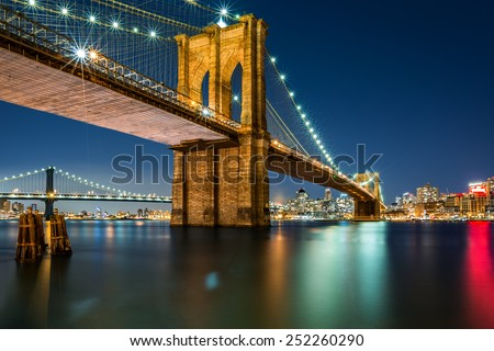 Illuminated Brooklyn Bridge by night as viewed from the Manhattan side - very long exposure for a perfectly smooth water - stock photo