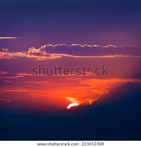 Illuminated by the sun clouds at sunset on a background of blue sky  - stock photo