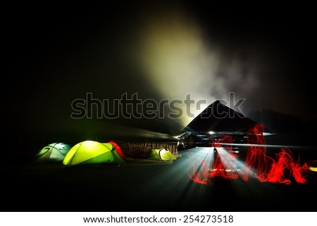 illuminated camping tents at night in alpin zone - stock photo