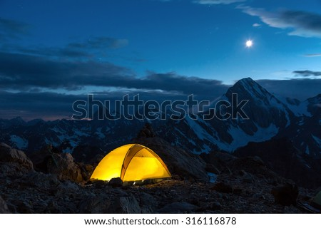 Illuminated Camping Yellow Tent Night High Altitude Alpine Landscape Shining Moon in Dark Blue Sky  - stock photo