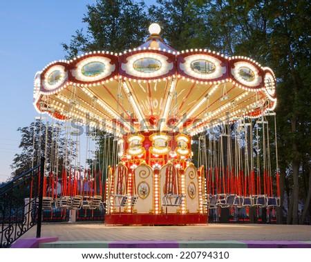 Illuminated carousel in amusement park - stock photo