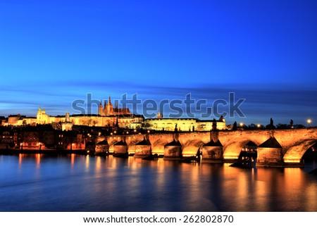 Illuminated Charles Bridge with Prague Castle at Dusk, Prague - stock photo