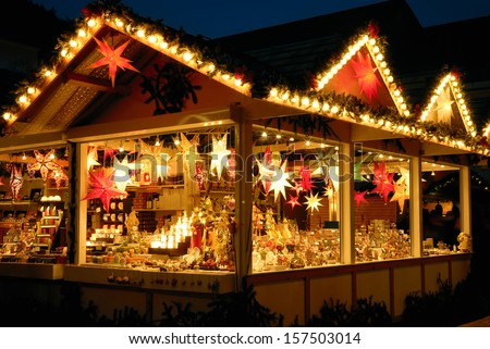 Illuminated Christmas fair kiosk with loads of shining decoration merchandise, no logos - stock photo