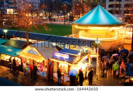 Illuminated Christmas fair with loads of movement, people in motion, no logos or faces - stock photo