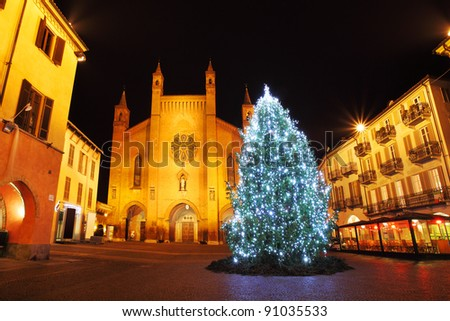 Illuminated Christmas tree on central plaza against San Lorenzo Cathedral in historic part of town of Alba, Italy. - stock photo