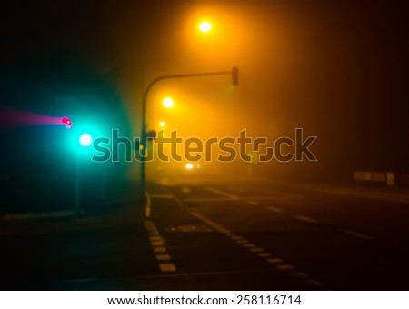 Illuminated city crossroads at night in fog. Abstract blurred cityscape. (blurred, toned) - stock photo