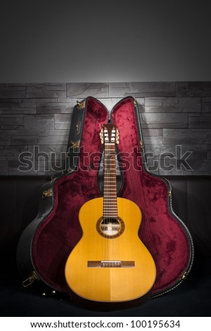 illuminated classic music guitar with case in front of leather and stone wall - stock photo