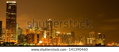 Illuminated commercial buildings at night in downtown Miami, USA.