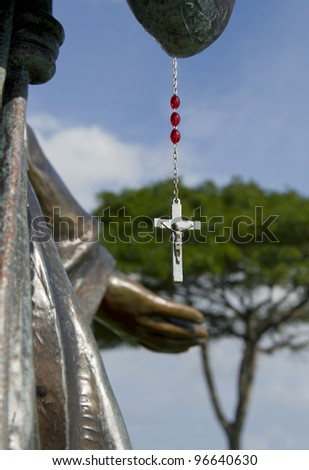 Illuminated cross with Jesus hangs from Virgin Mary statue with outstretched hands - stock photo