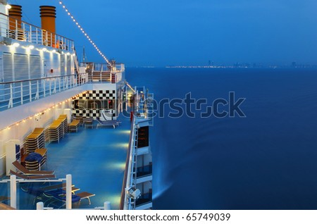 Illuminated cruise ship with people in the sea at night near city - stock photo