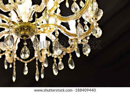 Illuminated crystal chandelier on dark ceiling