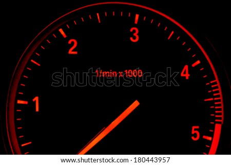 Illuminated diesel car tachometer isolated on black background