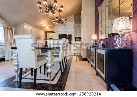 Illuminated dining room interior in luxury mansion - stock photo