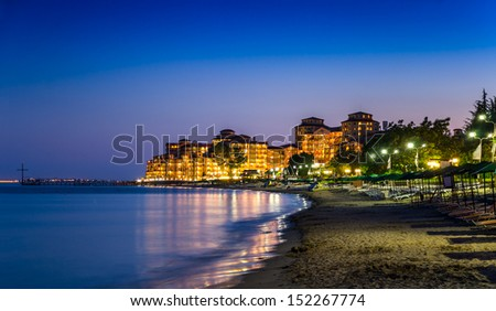 Illuminated Elenite at night, beach, hotels, sea, plank beds, umbrellas - stock photo