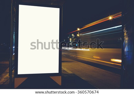 Illuminated empty billboard with copy space for your text message or content, public information board with blurred night lights on background, advertising mock up in outside, blank poster on roadside - stock photo