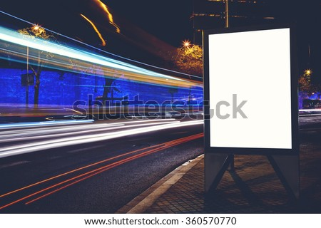 Illuminated empty electronic billboard with copy space for your text message or content, advertising mock up with movement of car on the background, blank public information board on roadside at night - stock photo