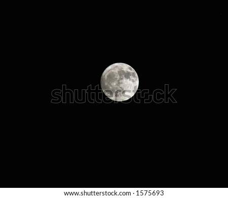 Illuminated full moon against black sky. - stock photo