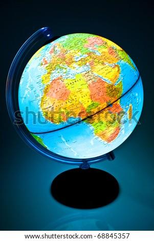 Illuminated Globe on a black backgroumd - stock photo