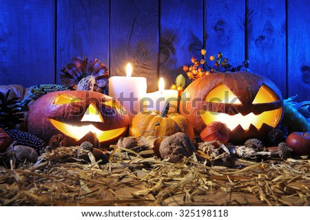 illuminated halloween pumpkins, candles, nuts, maize-cob and apple on straw in front of old weathered wooden board in blue sunset light - stock photo
