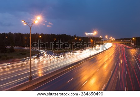 Illuminated highway at evening with light trails