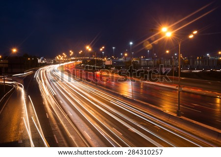 Illuminated highway at night with light trails