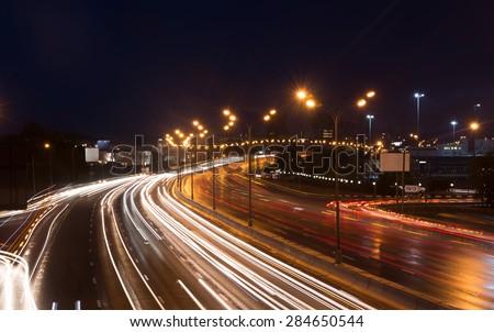 Illuminated highway at night with light trails - stock photo