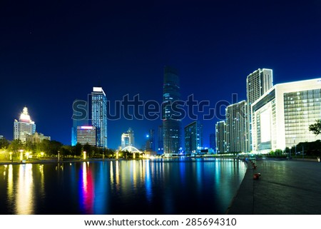 Illuminated modern skyscrapers and skyline at riverbank