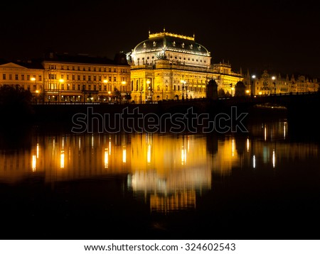 Illuminated National Theatre in Prague at night with reflection in Vltava River, Czech Republic