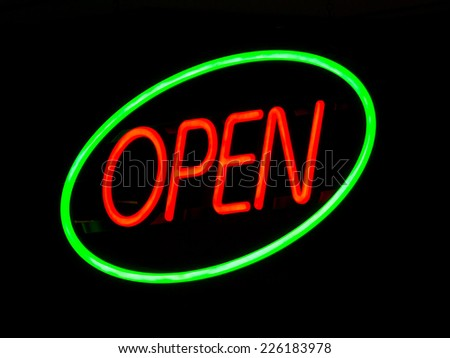 Illuminated neon open sign outside lit up at night on a shop window to advertise that the retail outlet is serving. - stock photo
