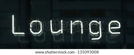 Illuminated neon sign Lounge in a window - stock photo