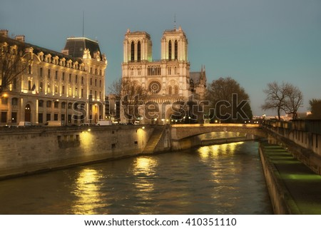 Illuminated Notre Dame de Paris Cathedral and Seine River at night. Focus on the round window of the cathedral. This image is toned. - stock photo
