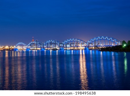 Illuminated railway bridge across the river Daugava, Riga, Latvia. Time shortly after the sunset