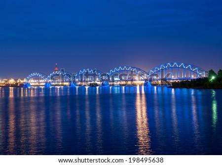 Illuminated railway bridge across the river Daugava, Riga, Latvia. Time shortly after the sunset - stock photo