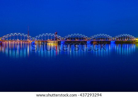 Illuminated railway bridge and reflection in Daugava river at twilight. Riga, Latvia - stock photo