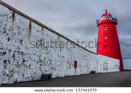 Illuminated red lighthouse and wall against a cloudy sky - stock photo