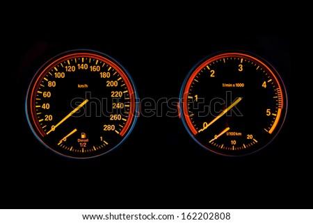 Illuminated speedometer and tachometer isolated on black background - stock photo