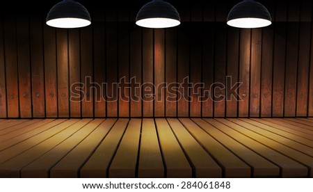 Illuminated spot lighting over dark background and wood floor - stock photo