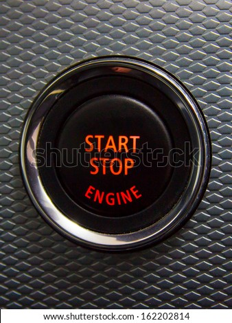 Illuminated Start Stop engine button in a sport car  - stock photo
