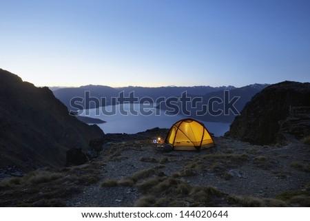 Illuminated tent by the lakeshore at dusk - stock photo