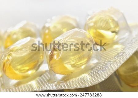 illuminated zoomed yellow transparent pills - stock photo