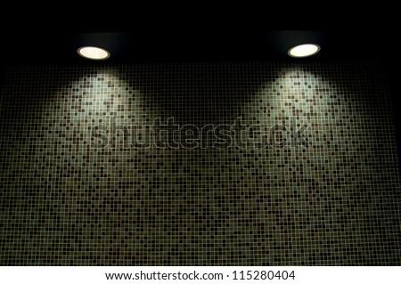 Illuminating pot-lights shining down on a tiled wall - stock photo