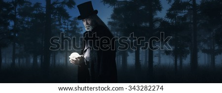 Illusionist Holding Illuminated Sphere in Foggy Winter Forest at Night. - stock photo