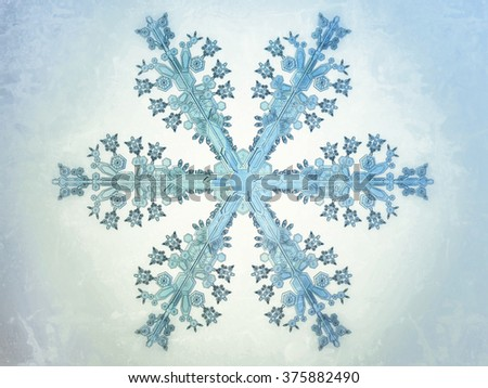 Illustrated closeup of a snowflake on a cold wintertime blue background