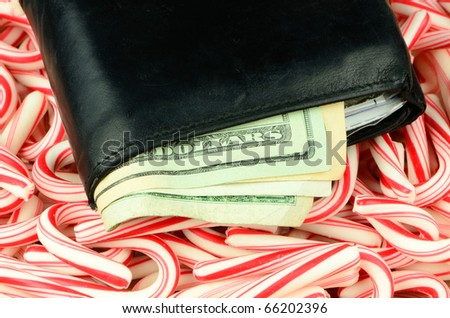 Illustrating the high cost of the Christmas holidays, a wallet full of money lies on a bed of candy canes. - stock photo