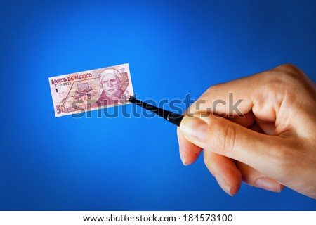 Illustration for inflation - hand with a pincer holding small banknote of Mexican peso, blue background - stock photo