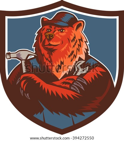 Illustration of a builder handyman Russian bear or Eurasian brown bear wearing hat arms folded with tools hammer and wrench facing front set inside crest shield done in retro woodcut style.  - stock photo