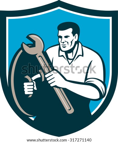 Illustration of a mechanic brandishing spanner wrench looking to the side viewed from front set inside shield crest on isolated background done in retro style.