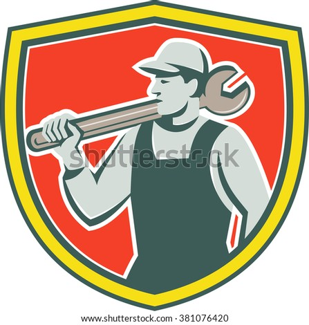 Illustration of a mechanic holding spanner on shoulder looking to the side set inside shield crest on isolated background done in retro style.  - stock photo