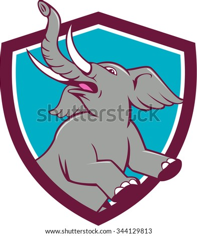 Illustration of an african elephant prancing looking up to the side set inside shield crest on isolated background done in cartoon style.