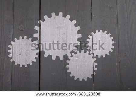 Illustration of white gears on dark black wooden background - stock photo